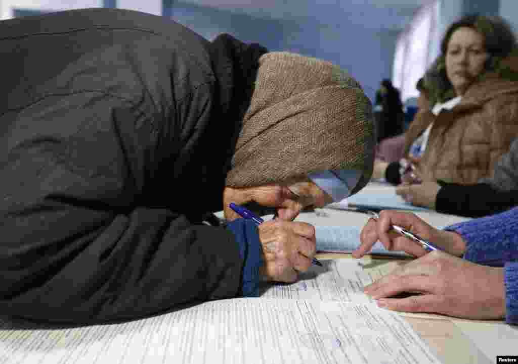 Пожилая женщина на избирательном участке в городе Славянске. 26 октября 2014 года.