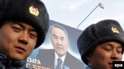 Kazakhstan -- Police officers walk in front of elections poster of President and Presidential candidate Nursultan Nazarbaev in Astana, 31Mar2011