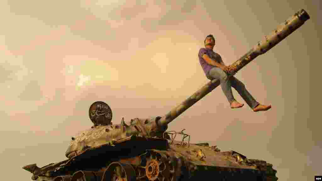 An Afghan youth sits astride the gun barrel of a Soviet-era tank in Kabul. (epa/Jawad Jalali)