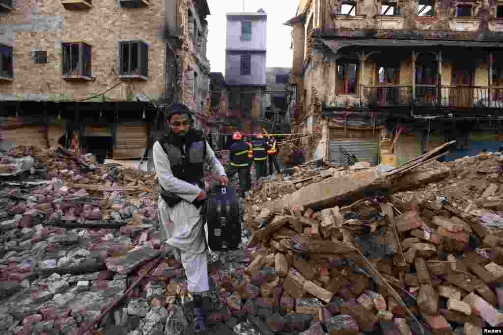 A man carries belongings recovered three days later from a building that burned down during sectarian clashes in Rawalpindi on November 15.