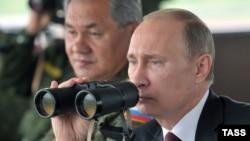 Президент Росії Володимир Путін та міністр оборони Сергій Шойгу (позаду)