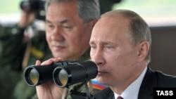 Президент России Владимир Путин (справа) и министр обороны России Сергей Шойгу наблюдают за ходом военных учений. Сахалин, 16 июля 2013 года.