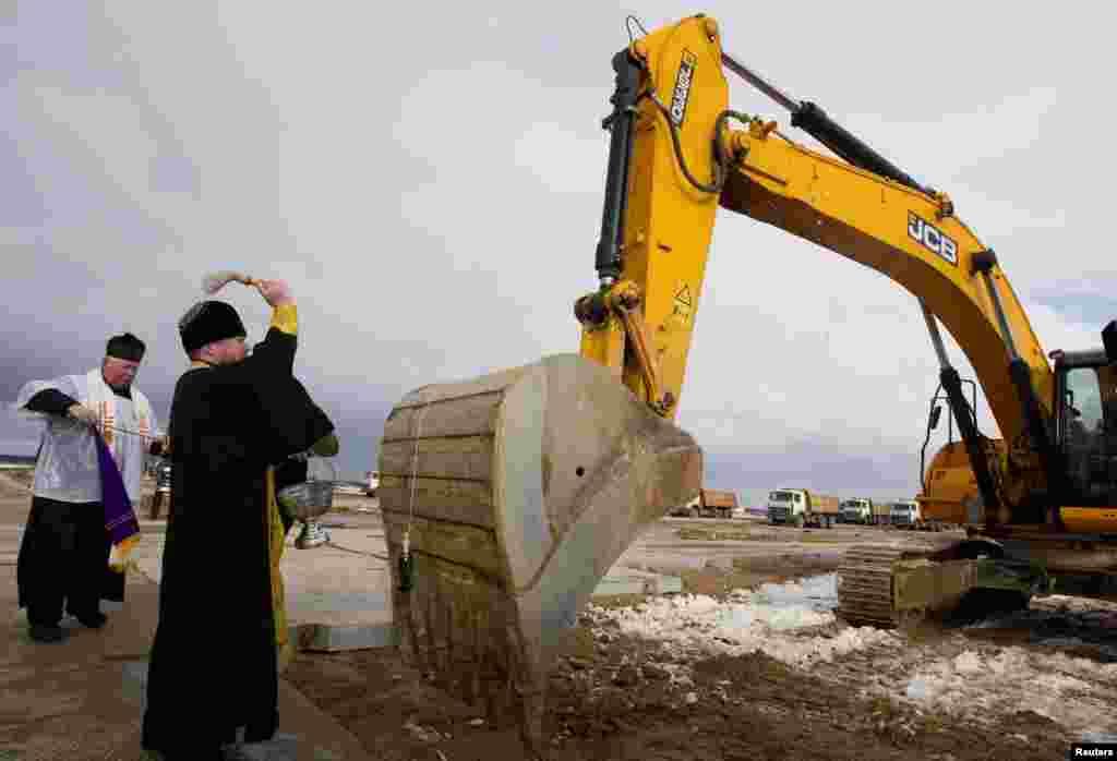 Un preot ortodox și unul catolic sfințesc un excavator la șantierul centralei nucleare de la Ostroveț, 1.02.2013.