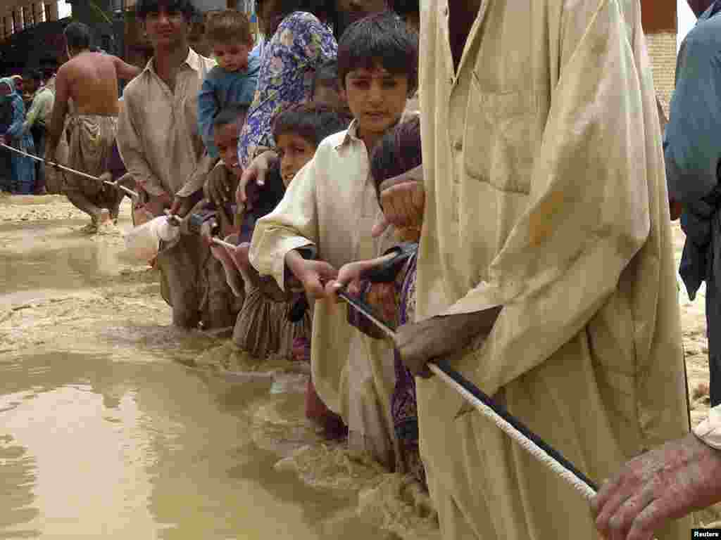 Residents cling to a rope as they walk through flood waters while evacuating the area after heavy rain in Pakistan's Baluchistan Province. Fifty people were killed when torrential rains unleashed flash floods in different parts of eastern Baluchistan. Photo by Reuters