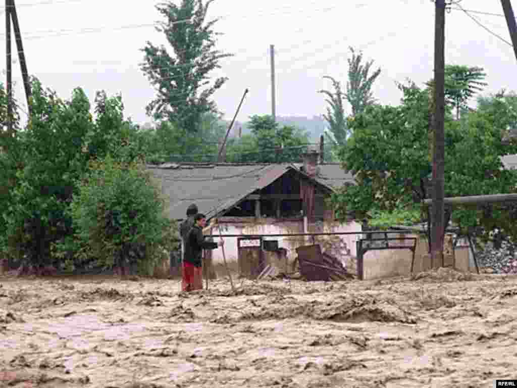 ...while men in the flooded Tajik village of Kulob resist being swept away. - Photo by RFE/RL