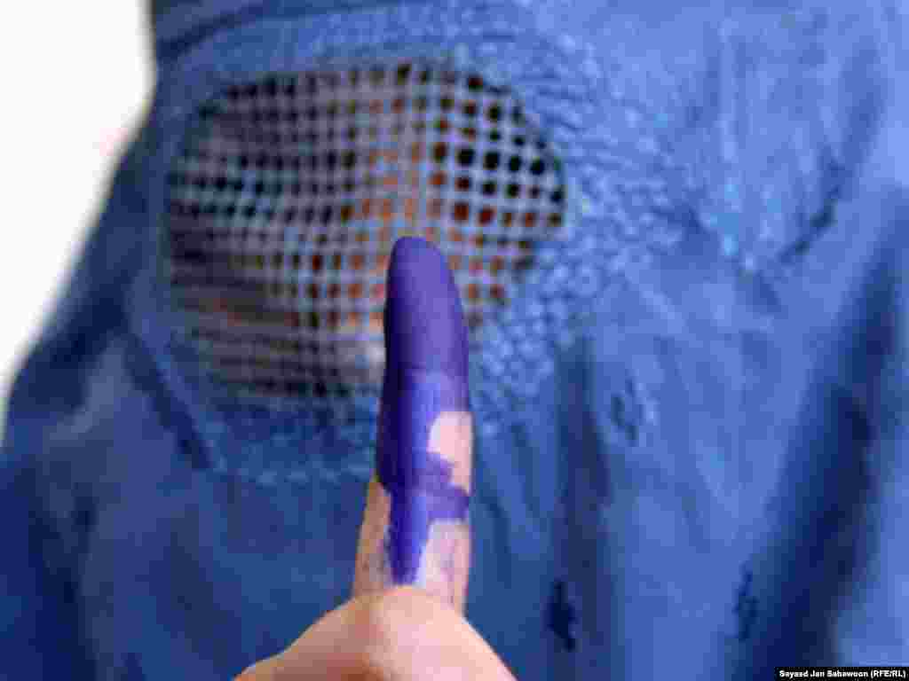 This Afghan woman shows her inked finger at a Kabul polling station.