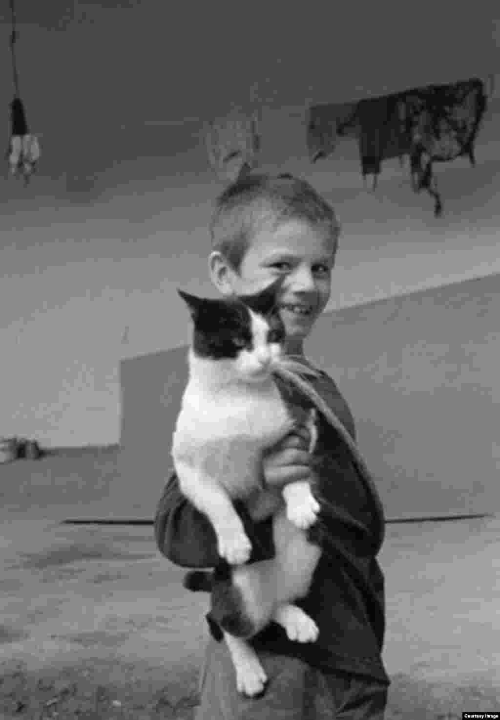 Мальчик Дока Узуев с котом в селе Итум-Кали.