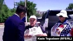 Сотрудник акимата города Усть-Каменогорска беседует с участниками акции протеста 77-летним Владимиром Тарасовым и его женой 72-летней Валентиной Тарасовой. Усть-Каменогорск, 12 июня 2018 года.