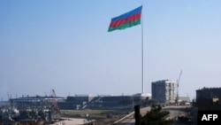 An enormous Azerbaijani flag flies above the Caspian Sea shoreline in Baku.
