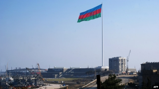 An enormous Azerbaijani flag flies above the construction site of the Crystal Hall on the Caspian shoreline in Baku earlier this year.