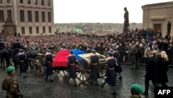 A caisson with the flag-draped coffin of former Czechoslovak dissident and Czech President Vaclav Havel arrives at Prague Castle on December 21, accompanied by his widow and surrounded by mourners.