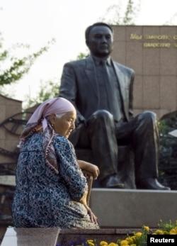 Пенсионерка у памятника Назарбаеву в Алматы.