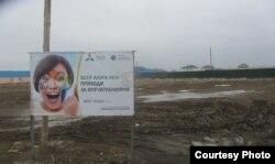 Баннер, рекламирующий выставку EXPO в Астане, стоит посреди бездорожья в Атырау.