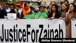 People hold signs to condemn the rape and killing of 7-year-old Zainab Ansari in Kasur, during a protest in Karachi on January 11.
