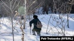 Лесник Болат Байгозиев пробирается через снег. Алматинская область, 1 марта 2019 года.