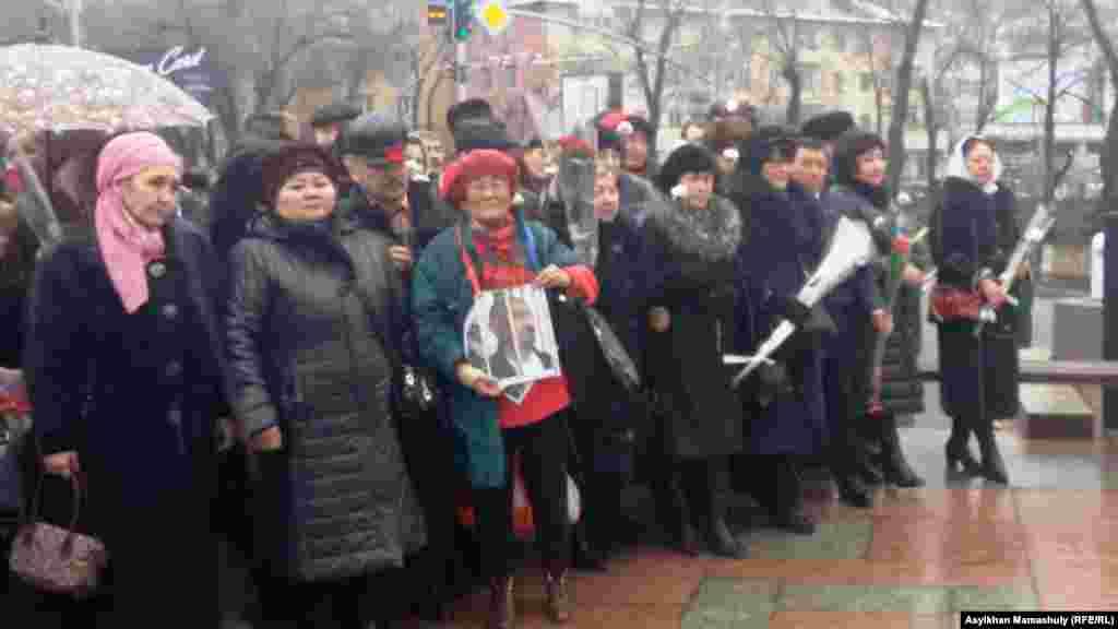 В центре собравшихся на церемонию можно увидеть гражданскую активистку Сахиб Жанабаеву. Она держит портрет диссидента Арона Атабека, более десяти лет находящегося в тюрьме после событий в поселке Шанырак вблизи Алматы в июле 2006 года.