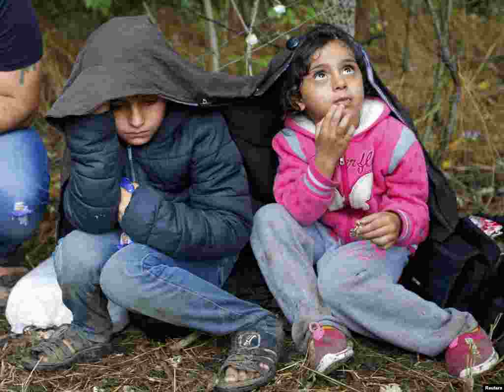 Children of Syrian migrants cover themselves from the rain as they rest on the side of a Hungarian road after crossing the border illegally from Serbia. (Reuters/Laszlo Balogh)