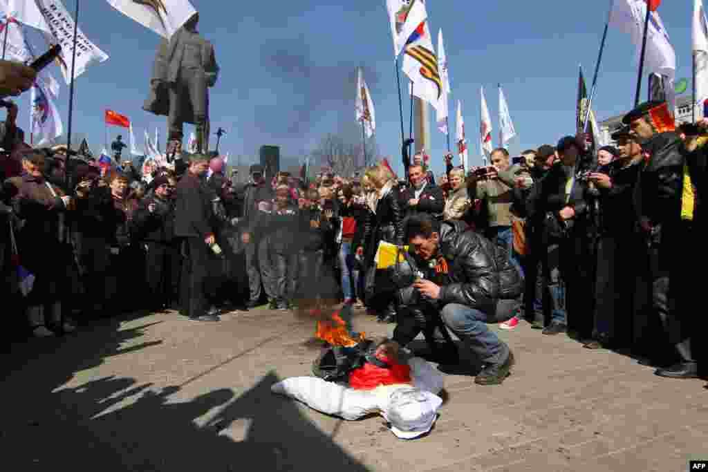 یکی از حامیان روسیه، در حال سوزاندن تصویر «استپان باندرا» است که یکی از چهره های اصلی استقلال اوکراین محسوب می شود