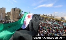 Syrian protesters wave their national flag as they demonstrate against the regime and its ally Russia in the rebel-held city of Idlib on September 7.