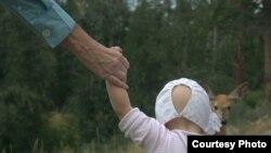 Мужчина держит за руку ребенка на ранчо для приемных детей в штате Монтана. 2011 год. Иллюстративное фото.