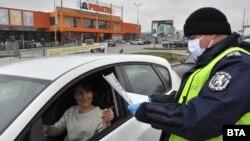 Полицай проверява деклаация на шофьорка на КПП на един от изходите от Хасково