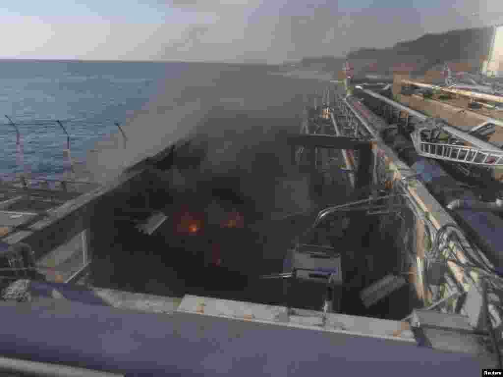 Foc și fum în zona unei clădiri folosite pentru prelevarea de probe din apa de mare lângă reactorul nr. 4 al centralei nucleare Fukushima Daiichi de la Tokyo Electric Power Co. din prefectura Fukushima pe 12 aprilie 2011.