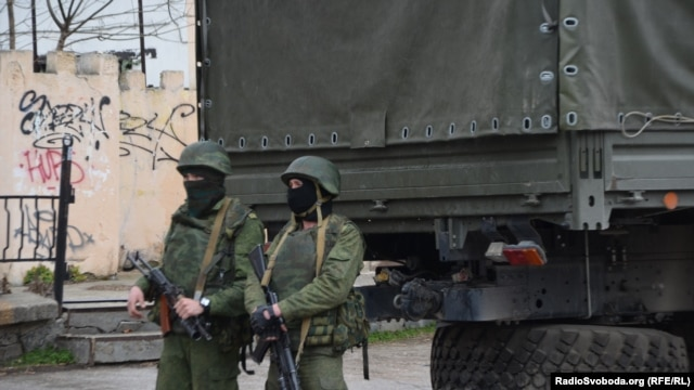 Armed men who are believed to be Russian troops on the streets of Simferopol.