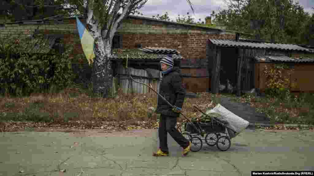 Местная жительница, 60-летняя Татьяна, таскает с окраин ветви деревьев, чтобы потом разжечь огонь в самодельной печи на улице.