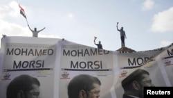Президент Мурсинин жактоочулары анын сүрөттөрүн жана өлкөнүн туусун көтөрүп, өкмөткө колдоосун билдиришүүдө. Александрия шаары. 2-июль 2013.