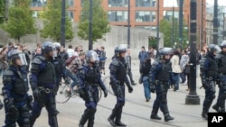 Riot police patrol after trouble on Market street in Manchester city center on August 9.