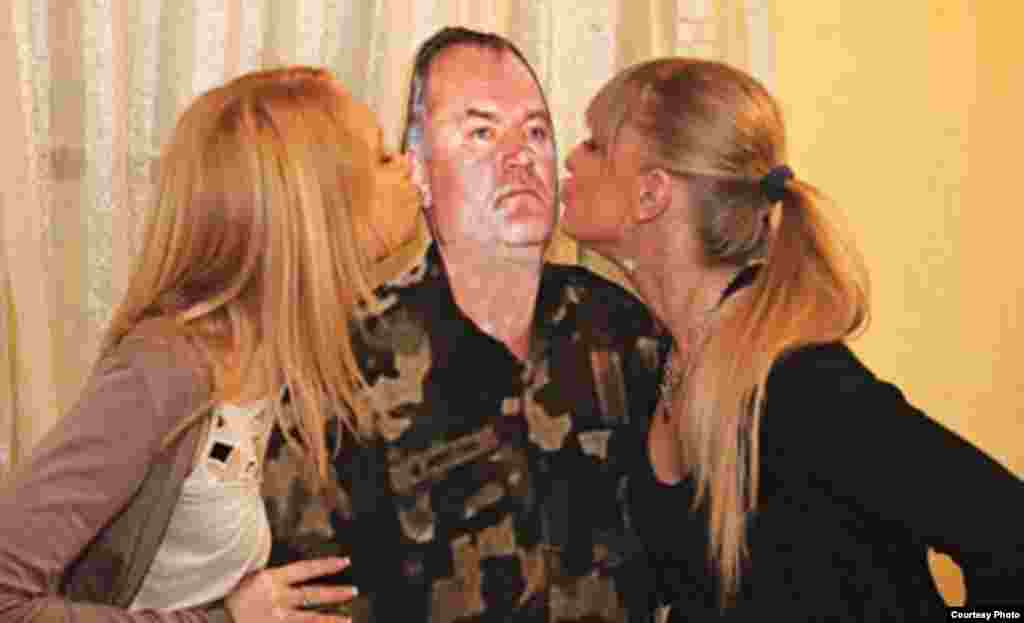 People celebrate Mladic's birthday by kissing a cardboard cutout in an event organized by the nationalistic organization Nasi in March 2011.