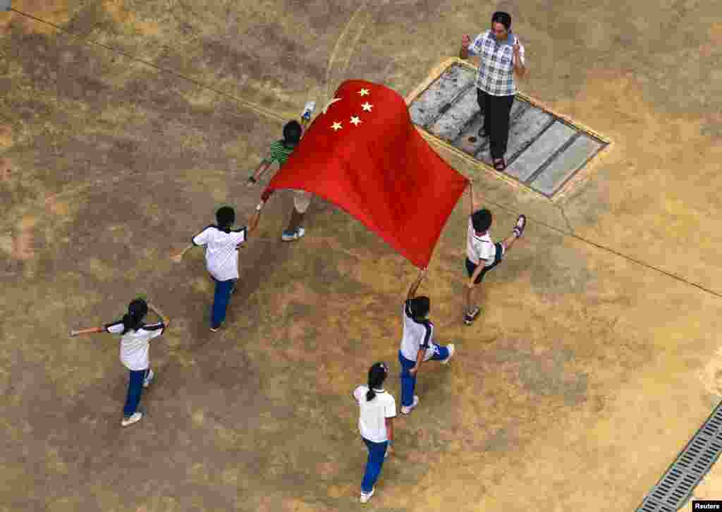 Students practice walking with the Chinese flag with their teacher in Guangzhou, Guangdong Province, China. (Reuters/Alex Lee)