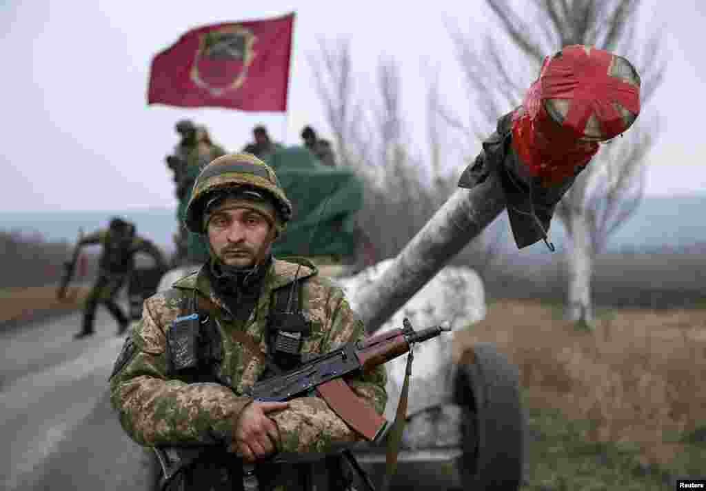 A member of the Ukrainian armed forces stands guard as a convoy of the Ukrainian armed forces prepare to move as they pull back from the Debaltseve region on February 26. Ukrainian troops towed artillery away from the front line, a move that amounted to recognizing that a cease-fire meant to take effect on February 15 appeared to be holding. (Reuters/Gleb Garanich)
