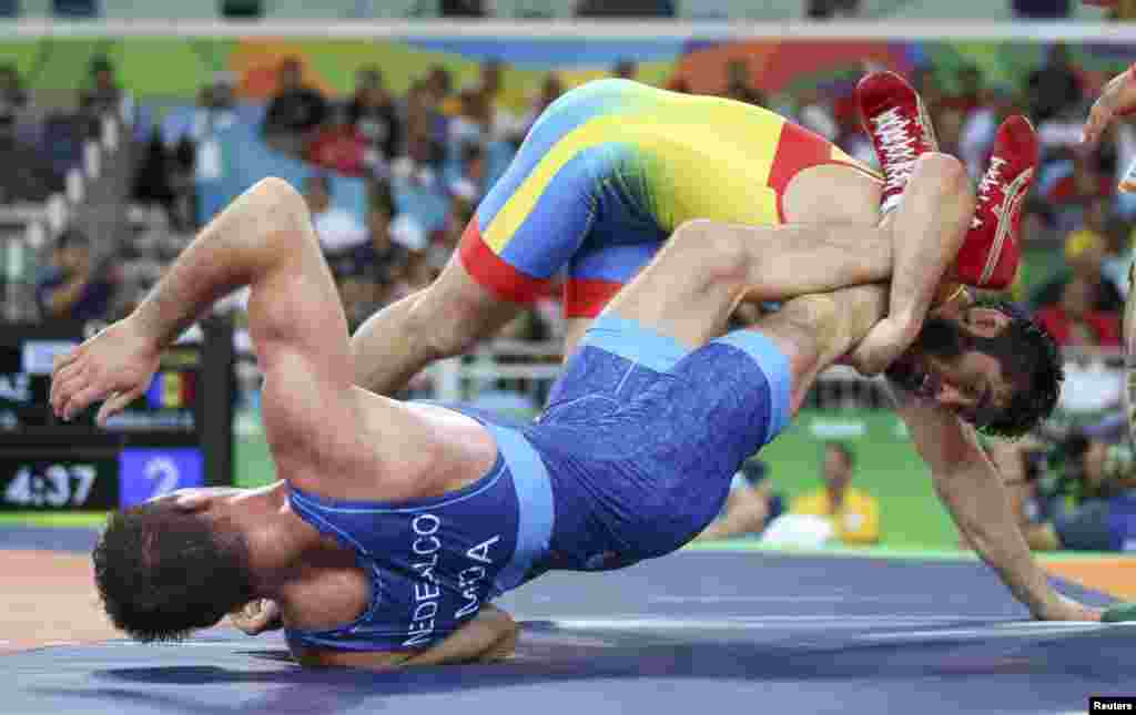 Wrestlers Galymzhan Usserbayev of Kazakhstan (top) and Evgheni Nedealco of Moldova compete in qualification for the men's freestyle 74-kilogram competition.