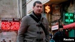 Люди проходят рядом с обменным пунктом в Москве. 17 декабря 2014 года.