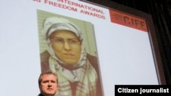 An image of Zhila Baniyaghoub flanks a presenter at an International Press Freedom Award event in Toronto in December 2009.