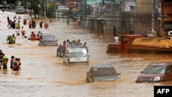 Motorists cross a flooded road in Marikina, east of Manila, on September 27.