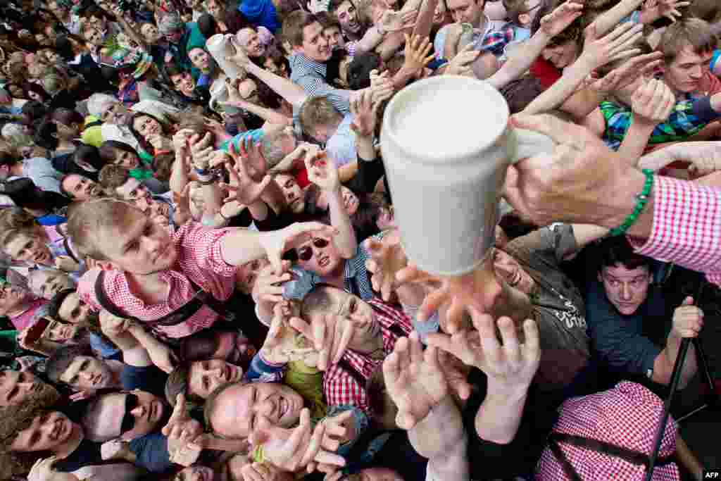 Visitors wait to receive the first beer in Erlangen, Bavaria, during the opening ceremony called Anstich of the traditional beer festival Bergkirchweih. The event is one of the biggest open-air beer gardens in Europe. (AFP/Daniel Karmann)
