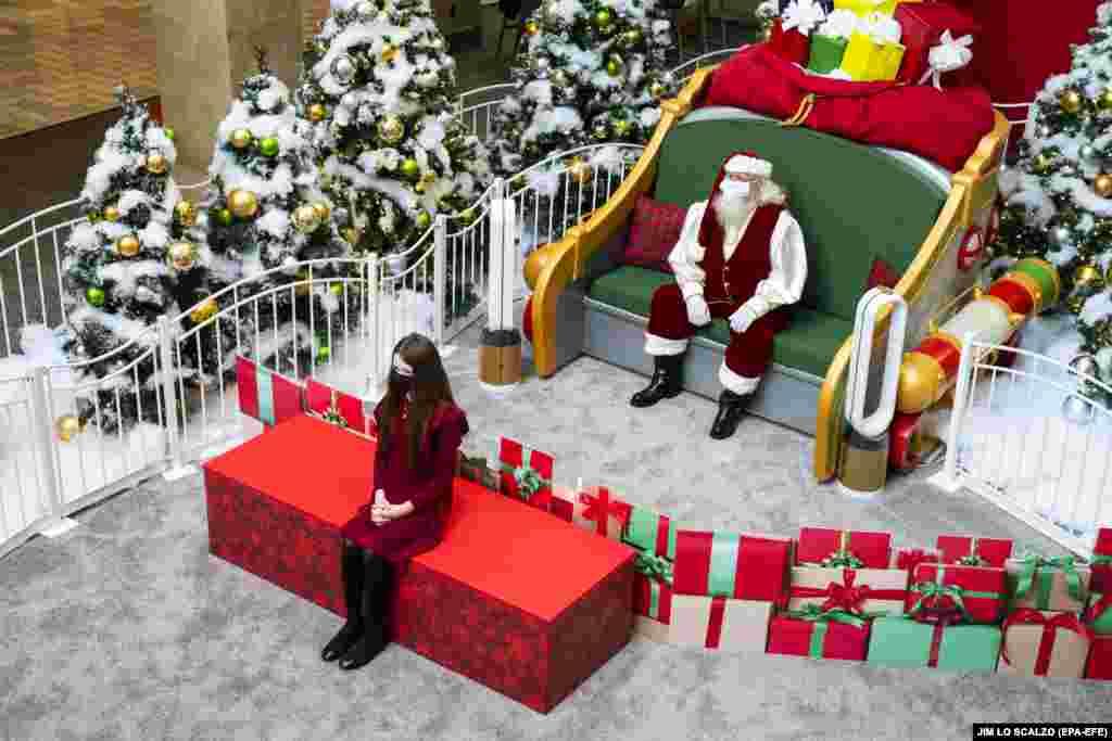Відвідувачка дотримується соціальної дистанції під час «безконтактного візиту до Санти» в «Тайсонс Корнер Центрі» (Tysons Corner Center). Тайсонс, Вірджинія, США, 3 грудня 2020 року