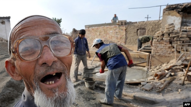 An ethnic Uzbek smiles as members of his family reconstruct their destroyed house in the village of Shark outside Osh, in October, 2010.