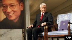 The chairman of the Nobel Committee, Thorbjoern Jagland, looks down at the vacant chair of Nobel Laureate Liu Xiaobo (pictured at left), on which Jagland placed the Nobel Peace Prize diploma and gold medal.