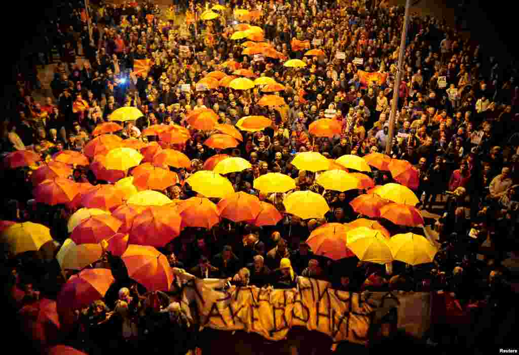 Protesters shout slogans while holding red and yellow umbrellas during demonstrations against an agreement that would ensure the wider official use of the Albanian language, in Skopje, Macedonia. (Reuters/Stringer)