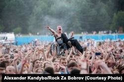 Əlil arabasında oturmuş Paval Konovalchik Minsk yaxınlığında keçirilən Rock Za Bobrov festivalında rəqs edir. Kütlə isə onu başı üzərində saxlayıb. 22 iyul, 2017. Foto: Alexander Kandybo/Rock Za Bobrov.