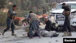 مردم و سربازان در حال کمک به یک زخمی پس از انفجاری در جلالآباد