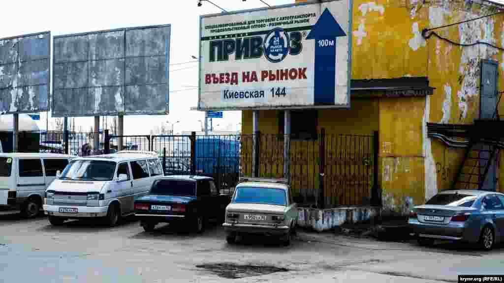 Крупная выбоина, облезлые стены и билборды – въезд на рынок Привоз