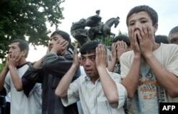 Люди моляться над тілами загиблих у протистояннях в Андижані, 14 травня 2005 року