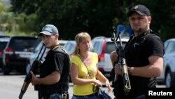 Një femër duke ecur afër dy pjesëtarëve të separatistëve prorusë në një lagje të qytetit Shakhtarsk