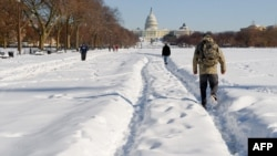 U.S. -- People walk through the snow-covered National Mall in Washington on 21Dec2009