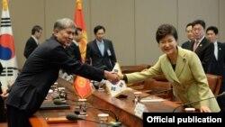 Пак Кын Хе Кыргызстандын мурдагы президенти Алмазбек Атамбаев менен жолуккан учур. Сеул, 2013-жылдын 19-ноябры.