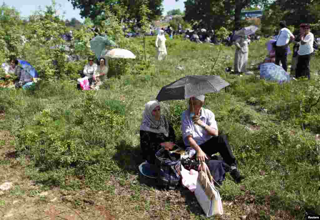 People wait for the ceremonial opening of the mosque on May 4.